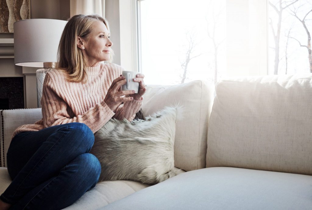 Woman-contemplating-on-couch-w-coffee-in-handock-961897192-1024×689